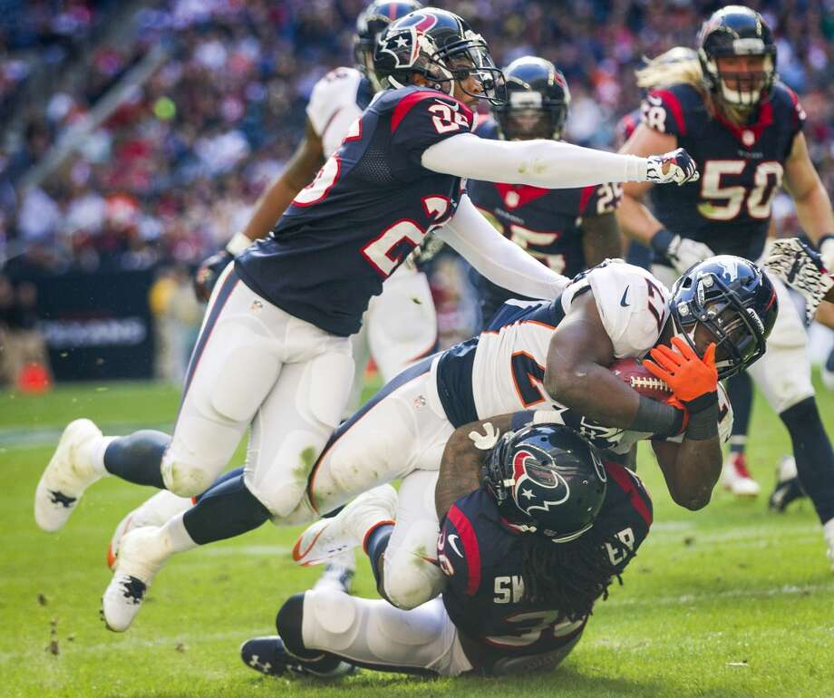 Broncos running back Knowshon Moreno dives forward as his is tackled by Texans strong safety D.J. Swearinger (36) and defensive back Brandon Harris. Photo: Brett Coomer, Houston Chronicle