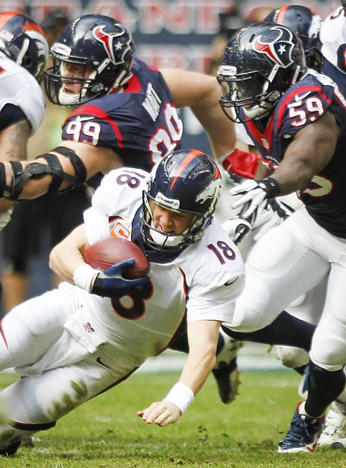 Broncos quarterback Peyton Manning  is sacked by Texans defensive end J.J. Watt and linebacker Whitney Mercilus. Photo: Brett Coomer, Houston Chronicle