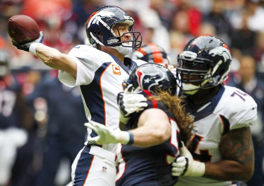 Broncos quarterback Peyton Manning releases a pass as he is pressured by Texans linebacker Brooks Reed. Photo: Brett Coomer, Houston Chronicle