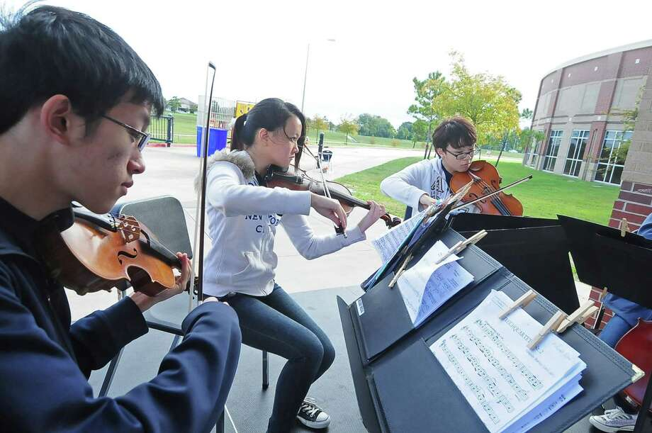 Michael Pan, 16, from left, and Helen Zhou, 14, play violin while Jerry Lee, 17, plays viola as their part in a string quartet of the Seven Lakes High School Orchestra during the Seven Lakes Orchestra's Parent Association eighth annual Pumpkin Patch Fest in October.  Michael Pan, 16, from left, and Helen Zhou, 14, play violin while Jerry Lee, 17, plays viola as their part in a string quartet of the Seven Lakes High School Orchestra during the Seven Lakes Orchestra's Parent Association eighth annual Pumpkin Patch Fest in October. Photo: Â Tony Bullard 2013, Freelance Photographer / © Tony Bullard & the Houston Chronicle