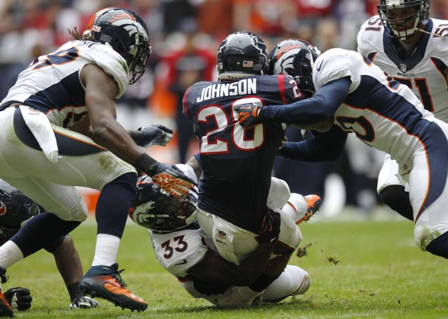 Texans running back Dennis Johnson (28) is stopped by Broncos strong safety Duke Ihenacho (33) and strong safety Mike Adams (20). Photo: Brett Coomer, Houston Chronicle