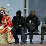 Rocky Lam dressed as Chai Shun the God of Fortune takes a break as he waits for the parade to begin, as San Francisco's Chinese New Year parade prepares to makes it's way through downtown on Saturday Feb. 23, 2013.