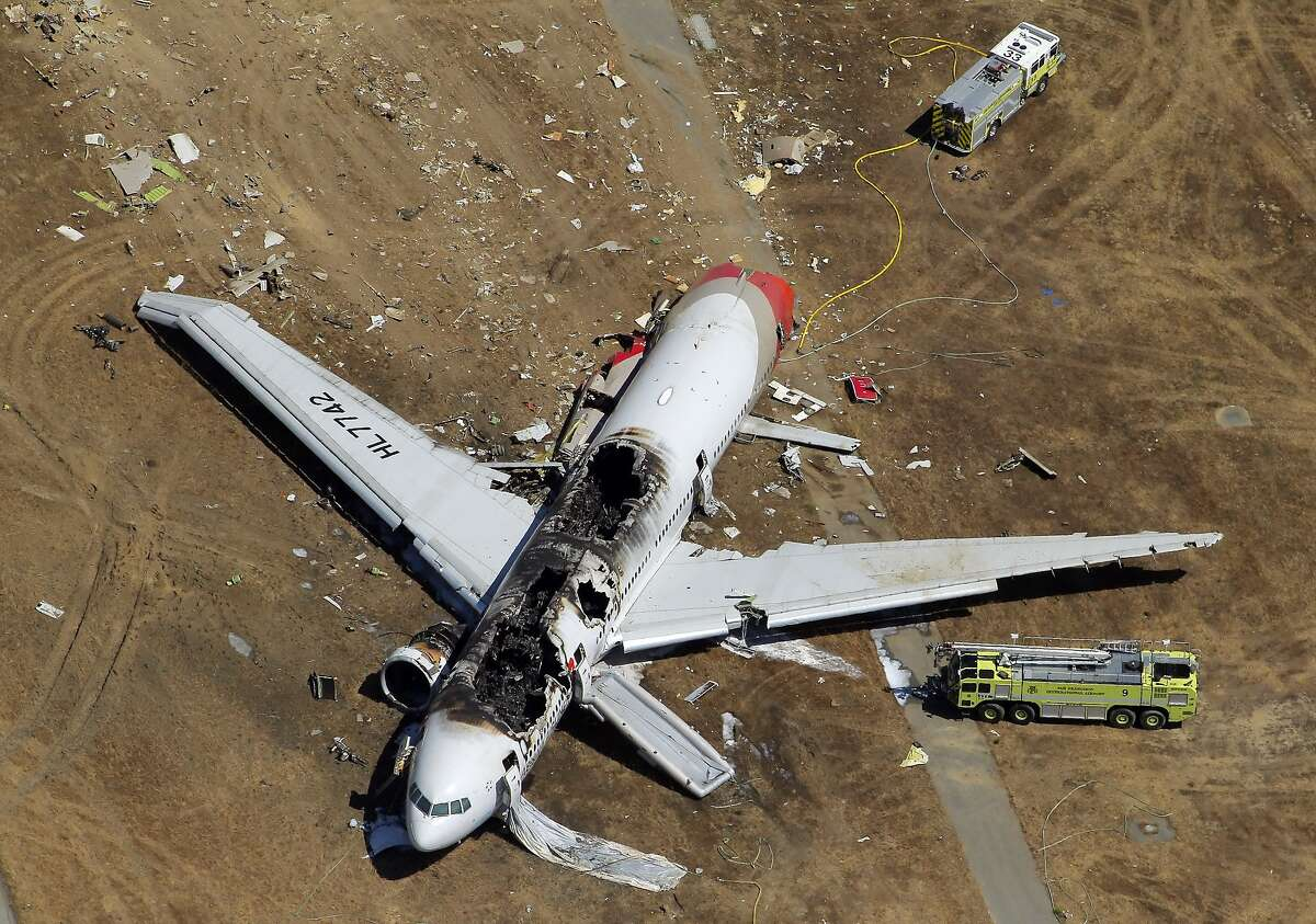 The destroyed fuselage of Asiana Airlines Flight 214 is visible on the runway at San Francisco International Airport after it crashed on landing and burned on Saturday, July 6, 2013.