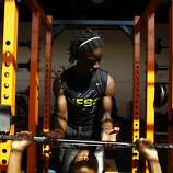 Lewis Otis helps Mike Walker lift his reps as they work out in the weight room before football practice at Mcclymonds high school on Monday, August 05, 2013 in Oakland, Calif.