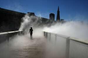 "A pedestrian walks across ""Fog Bridge"", a 150 foot long bridge next to the Exploratorium by artist Fujiko Nakaya in San Francisco, California, during a warm sunny day on Monday, September 23, 2013."