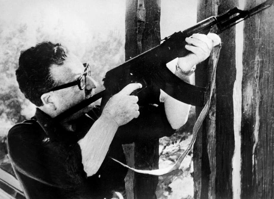 1971: Chilean President Salvador Allende testing a Kalashnikov machine gun given to him as a gift by then-Cuban President Fidel Castro. Photo: STR, Getty Images / 2011 AFP