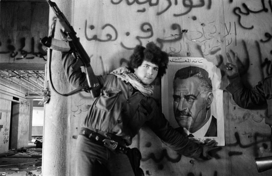 1976: A Palestinian fighter sticks a portrait of Egyptian President Nasser on the wall of Holiday Inn hotel after Palestinian commando units dislodged Lebanese Christian forces from the 27-story hotel. Photo: XAVIER BARON, Getty Images / 2010 AFP