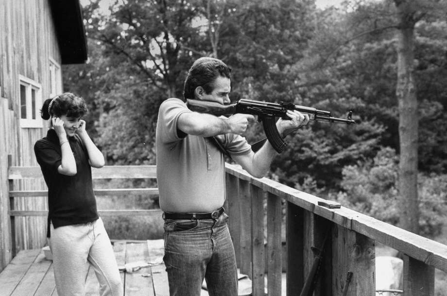 1988: Frederick Hone, who married 17-year-old former sixth grade student of his, using an AK-47 in target practice on porch in back yard as his young wife Kimberly watches while plugging her ears. Photo: Steve Liss, Getty Images / Steve Liss