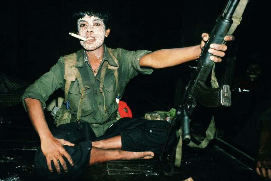 1988: A Mon National Liberation Army soldier posing with his gun, a cheroot and tanaka powder on his face during a night stop while on a mission in Mon state in Burma. Photo: Thierry Falise, Getty Images / © 1988 Thierry Falise