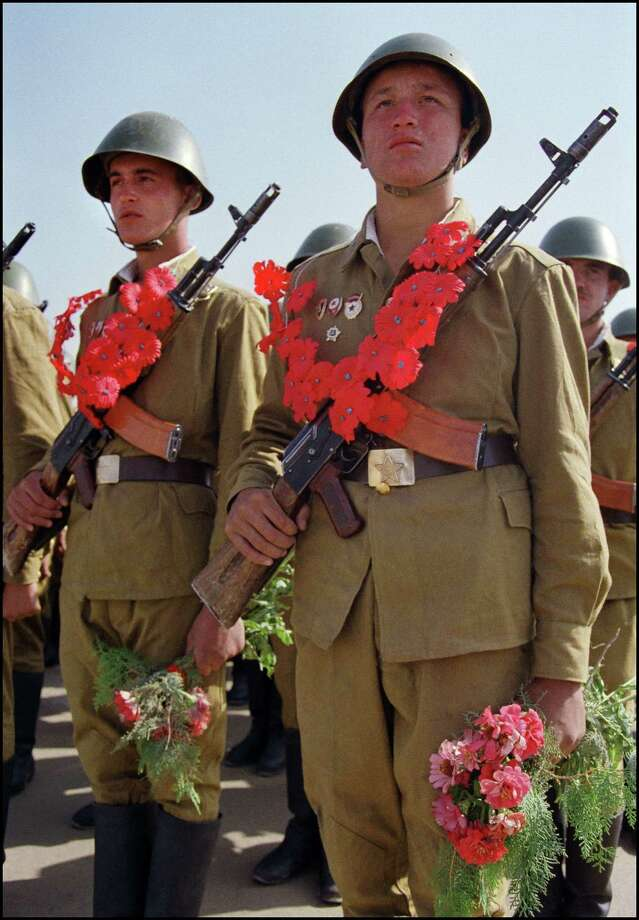 1986: Red Army soldiers wearing paper garlands holding their AK-74 Kalashnikov assault rifles and bouquets of red carnations, wait for their plane to leave Kabul, Afghanistan, for the Soviet Union. Photo: DANIEL JANIN, Getty Images / 2012 AFP
