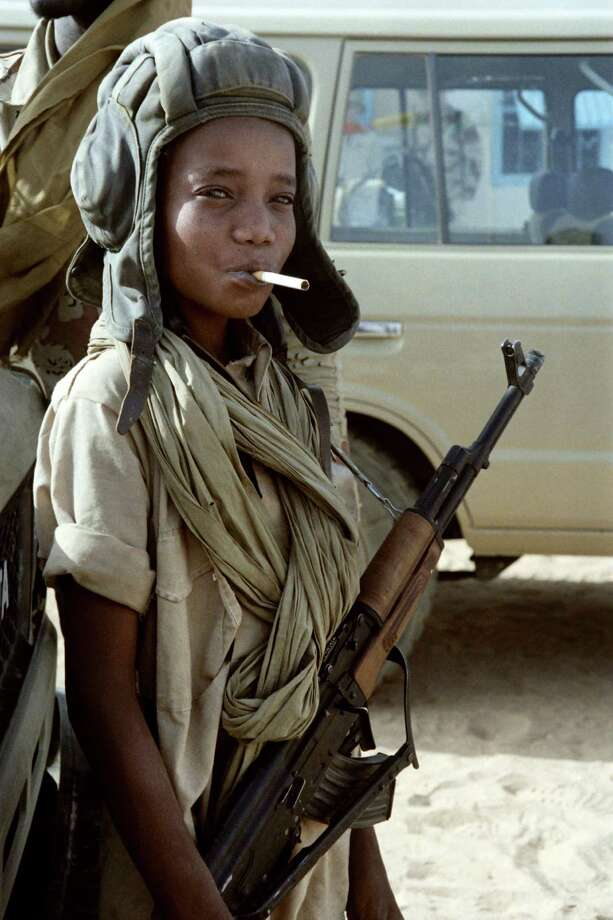 1987: A child soldier poses with a Libyan helmet, a cigarette and a Soviet-made AK-47 Kalashnikov in Kalait after the defeat of Libyan army during the Chadian-Libyan conflict. Photo: DOMINIQUE FAGET, Getty Images / 2011 AFP