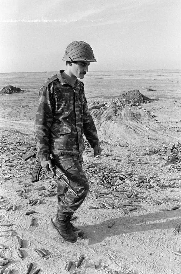 1985: A helmeted, Kalashnikov-armed Iraqi soldier walks among cartridges in the area of the al-Howeizah marshes, Southern Iraq, after his unit clashed violently with Iranian forces which tried to cut the Baghdad-Basra road. Photo: JEAN-CLAUDE DELMAS, Getty Images / 2010 AFP