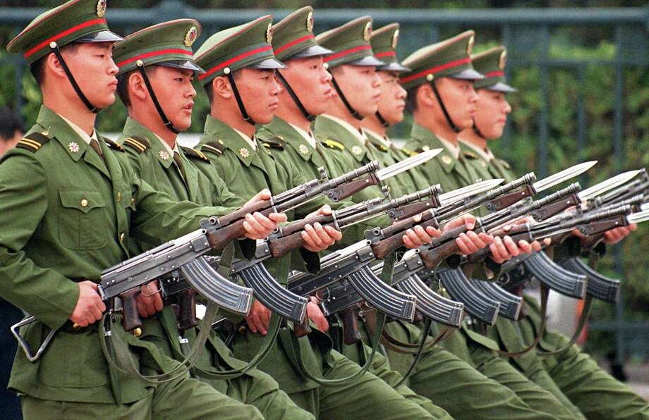 1998: People's Liberation Army soldiers march in formation with their bayonetted Kalashnikov rifles at the Great Hall of the People, across the street from Tiananmen Square in Beijing. Photo: STEPHEN SHAVER, Getty Images / 2011 AFP
