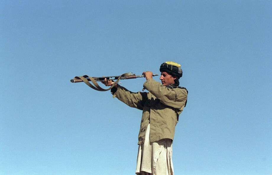 1996: A soldier belonging to a Taliban militia looks down the barrel of his AK-477 assault rifle to check for dirt on the front line north of Kabul. The Taliban warriors, who are believed to have emerged from religious seminaries, or madressas, in Pakistan, took to the Afghan scene in 1994, captured Kabul in 1996 and control two-thirds of Afghanistan, which has been at war for 20 years following the Soviet invasion of 1978. Photo: EMMANUEL DUNAND, Getty Images / 2011 AFP