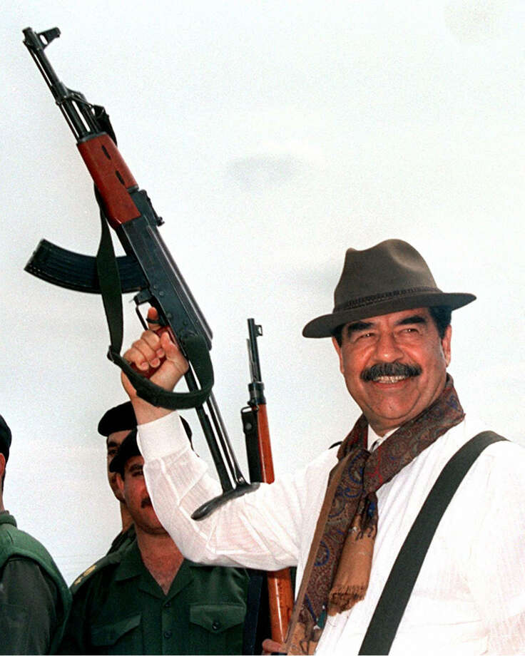 1998: Saddam Hussein brandishes a Russian-made AK-47 assault rifle during his visit to villages in northern Iraq. Photo: AFP, Getty Images / 2006 AFP
