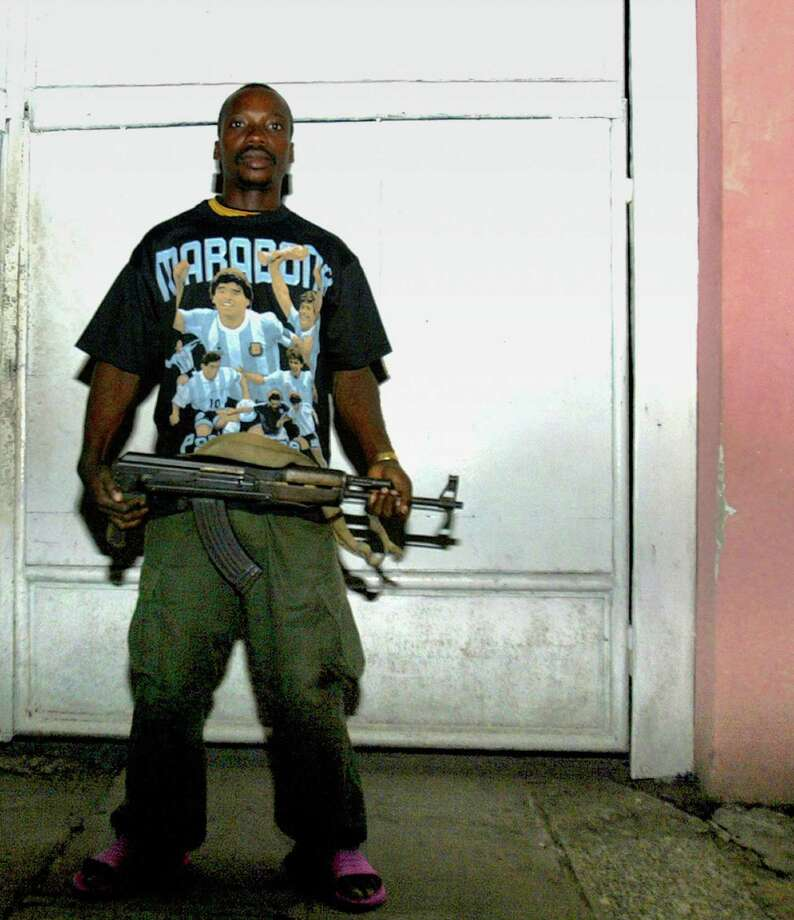 2005: A Congolese soldier wearing a Maradona t-shirt and carrying an AKM assault rifle keeps watch at the residence of a Congolese Army colonel in the Gombe neighborhood in Kinshasa, Democratic Republic of Congo. Photo: STF, Getty Images / 2005 AFP