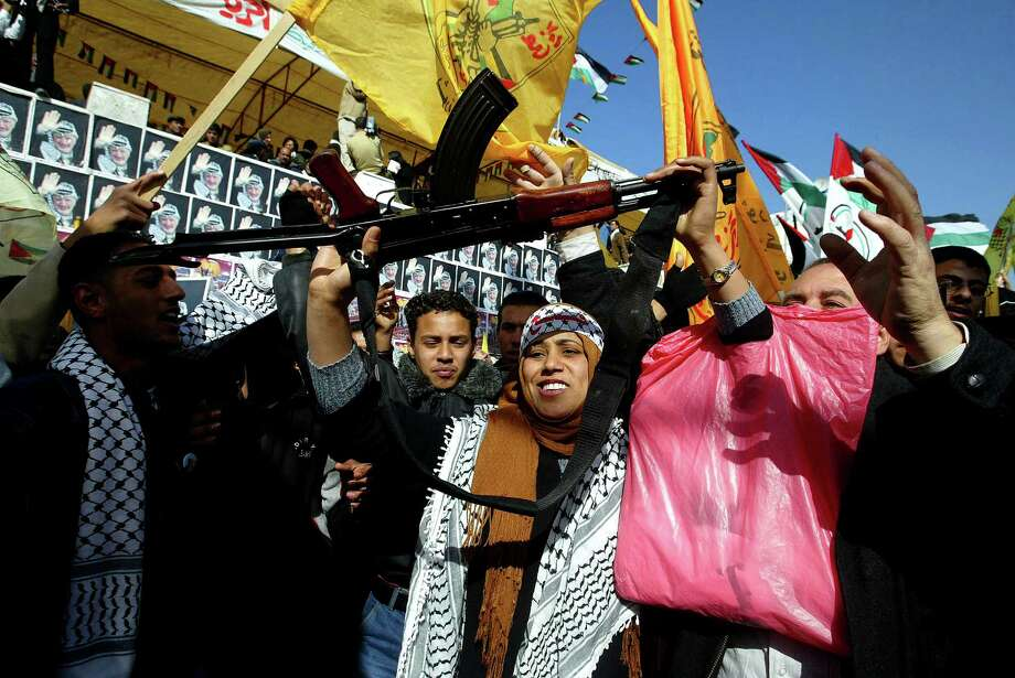 2003: A Palestinian woman dances with an AK-47, during a rally to mark the 39th anniversary of the Palestinian National Liberation Movement's (Fatah) foundation on December 31, 2003 in Gaza City, Gaza Strip. Tens of thousands of Palestinians gathered at the Palestinian Legislative council to mark the anniversary of the 1965 founding of Fatah. Photo: Abid Katib, Getty Images / 2003 Getty Images