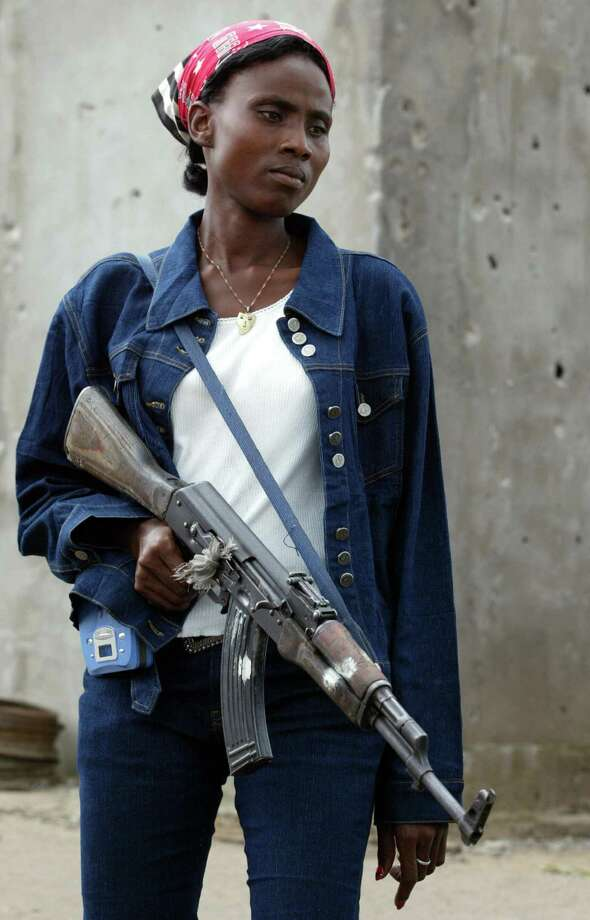 2003: A woman soldier with Liberians United for Reconciliation and Democracy holds an AK-47 as she waits at a checkpoint. Photo: GEORGES GOBET, Getty Images / 2003 AFP