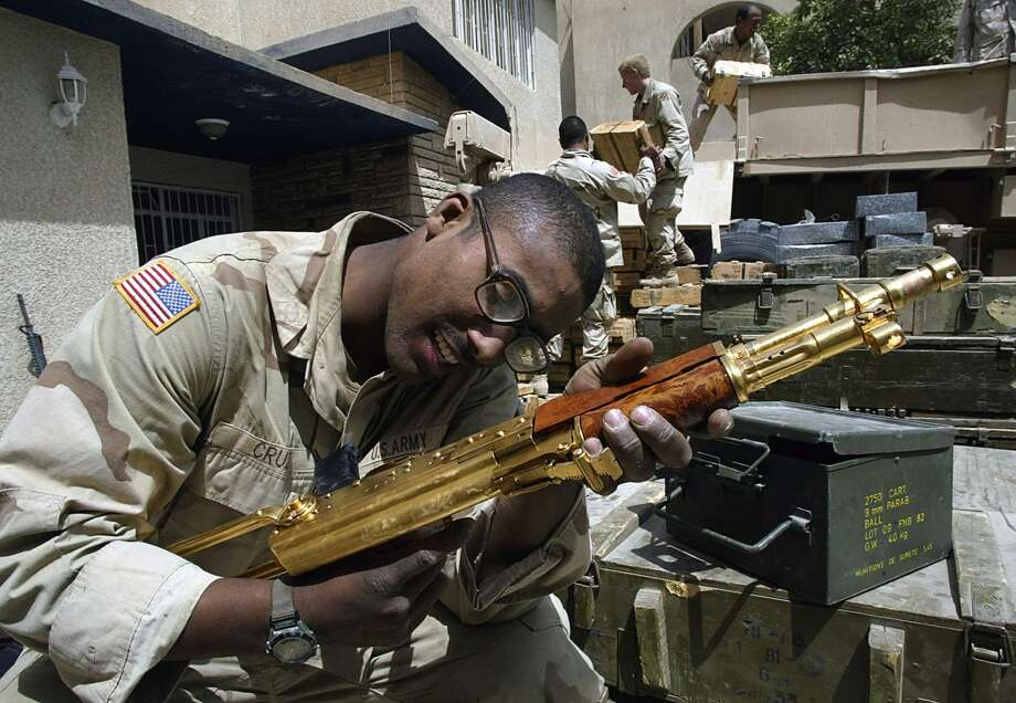 "2003: A US soldier from the 3rd Infantry Division takes a close look at a golden Kalashnikov engraved with an Arabic sentence reading ""A gift from Iraqi President Saddam Hussein."" Photo: ODD ANDERSEN, Getty Images / 2009 AFP"
