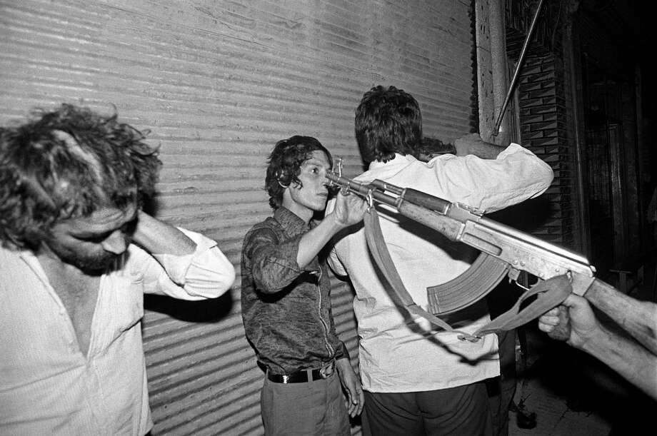 1982: A drug user is arrested and held at gunpoint by a drug squad in the Shahr-e No district of Tehran, Iran. Photo: Kaveh Kazemi, Getty Images / 2009 Getty Images