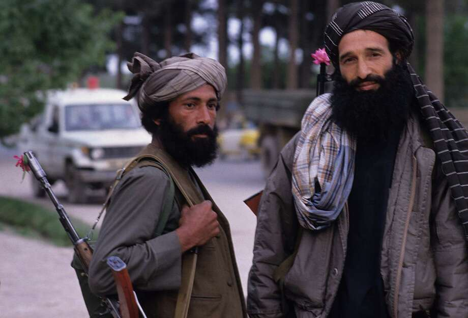 1992: Two Mujahedeen with flowers in the barrels of their AK-47s, guard a crossroads in Herat, Afghanistan, shortly after they retook the city from the Soviet backed communist regime of Mohammad Najibollah. Photo: Kaveh Kazemi, Getty Images / 2009 Getty Images