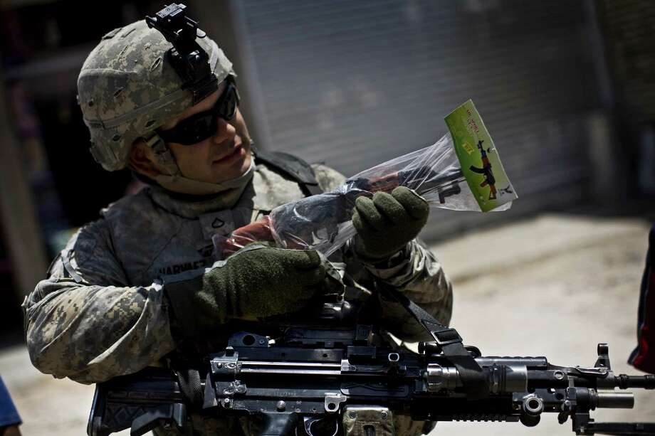 2008: An American soldier plays with a toy AK-47 while on patrol in Sadr City, Iraq. Photo: Benjamin Lowy, Getty Images / 2008 Benjamin Lowy