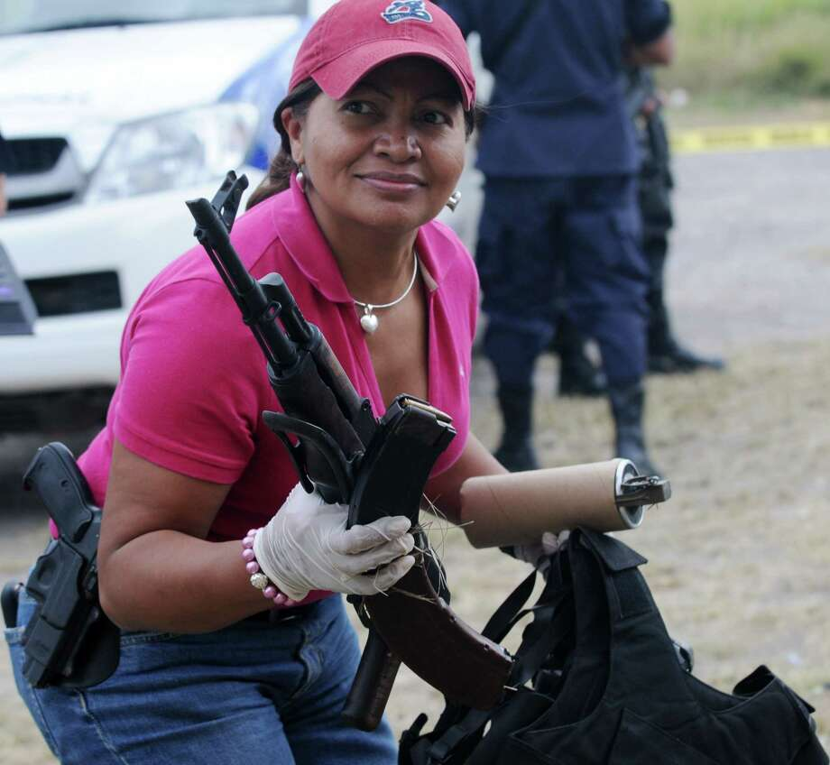 2011: A criminal investigation agent holds the AK-47 and a tear gas bomb belonging to the seven captured man with an AK-47, 9mm guns, tear gas bombs, gas masks, bulletproof vests and cell phones north of Tegucigalpa, Honduras. Photo: ORLANDO SIERRA, Getty Images / 2011 AFP