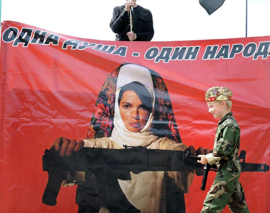 "2009: Russian and South Ossetian activists shout anti-Georgian slogans in central Moscow behind a poster showing an Ossetian woman offering a Kalashnikov and reading ""One people - one soul."" Photo: ALEXANDER NEMENOV, Getty Images / 2011 AFP"