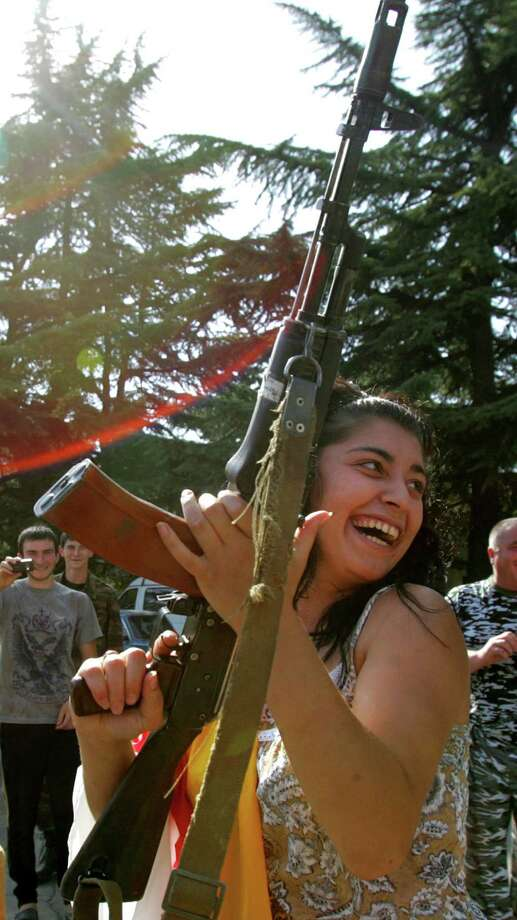 2008: A resident of Tskhinvali holds a Kalashnikov as she celebrates the recognition of South Ossetian independence by the Russian Federation. Photo: VIKTOR DRACHEV, Getty Images / 2011 AFP