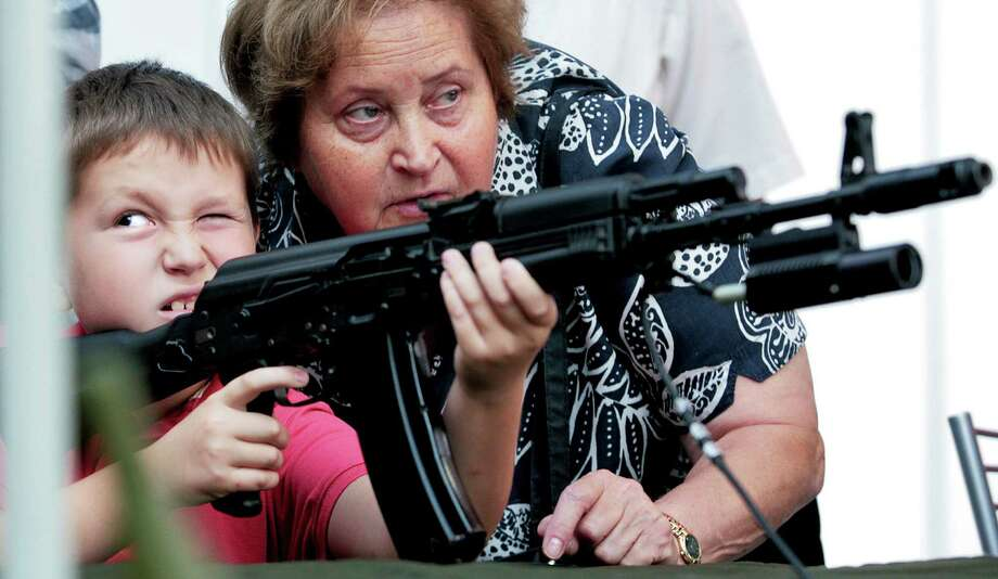 2008: A boy aims with a fake Kalashnikov as his grandmother assists him at a weapons fair in Moscow. Photo: SERGEI SHAKHIJANYAN, Getty Images / 2011 AFP