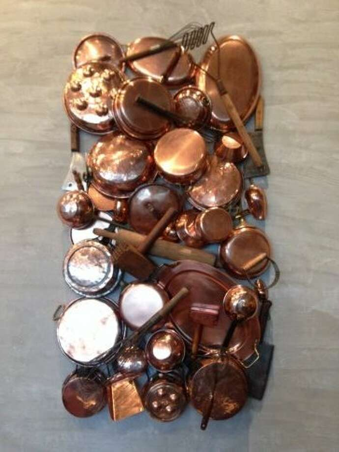 Custom art installation made from copper pots, antique wooden mallets and chef tools at Vallone's.