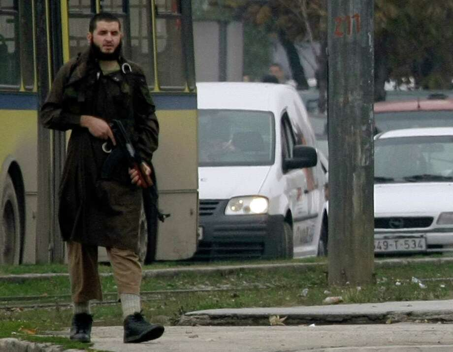 2011: Mevlid Jasarevic stands at an intersection holding an AK-47, after opening fire upon the U.S. embassy in Sarajevo. Photo: ELVIS BARUKCIC, Getty Images / 2011 AFP