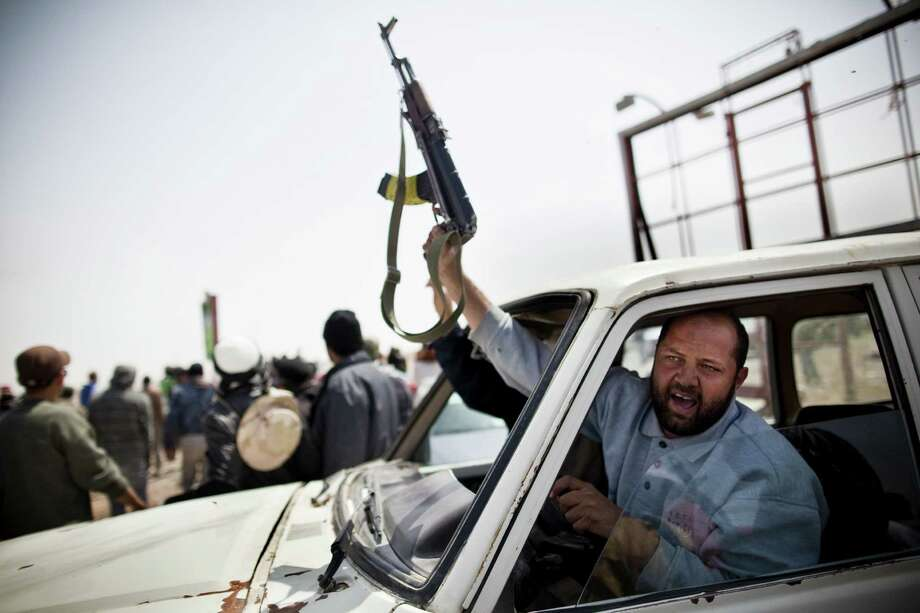 2011: A Libyan rebel celebrates the fall of Ajdabiya by firing his AK-47 through his windshield-less car. Photo: Benjamin Lowy, Getty Images / 2011 Benjamin Lowy