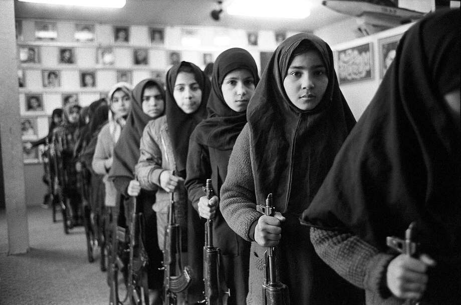 1988: Schoolgirls in Islamic veils go through arms training as a Basijis while holding AK-47 automatic assault rifles and standing in front of pictures of martyrs of Iran-Iraq conflict in a mosque in Tehran. Photo: Kaveh Kazemi, Getty Images / 2010 Kaveh Kazemi