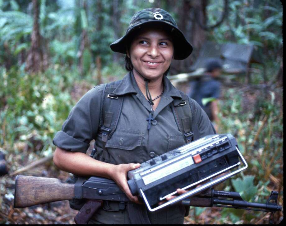 1983: With an AK-47 assault rifle over her shoulders, a Contra fighter smiles as she listens to a boom box at a base camp in Honduras. Photo: Steven Clevenger, Getty Images / Hulton Archive