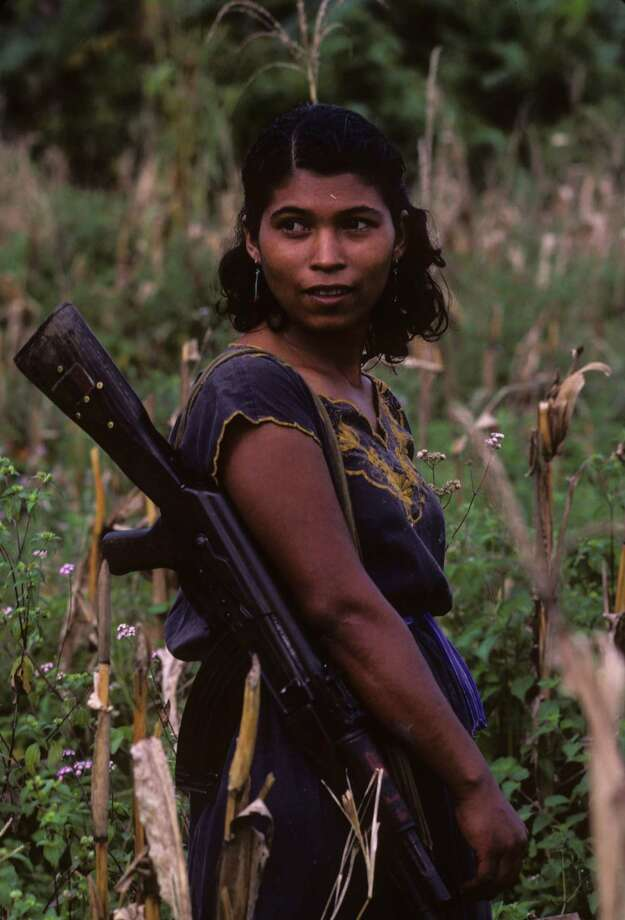 1986: A female Nicaraguan farmer armed with AK-47 assault rifle works on a cooperative farm in Jinotega on the Honduran border. Photo: Kaveh Kazemi, Getty Images / 2010 Getty Images