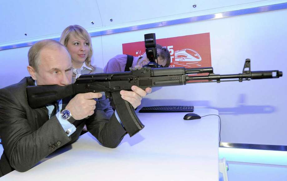 2012: Vladimir Putin aims at a target with a replica of Kalashnikov assault rifle in Moscow. Photo: ALEXEY DRUZHININ, Getty Images / 2012 AFP