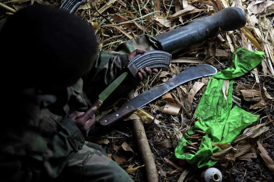 2013: A MauMau Nyatura fighter services an AK-47 magazine in a hut at a hilltop base in Kiseguro, in the east of the Democratic Republic of the Congo. Photo: PHIL MOORE, Getty Images / 2013 AFP