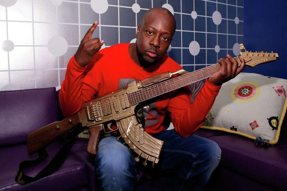 2013: Wyclef Jen poses backstage with a guitar shaped like a AK-47 in New York City. Photo: JP Yim, Getty Images / 2013 Getty Images