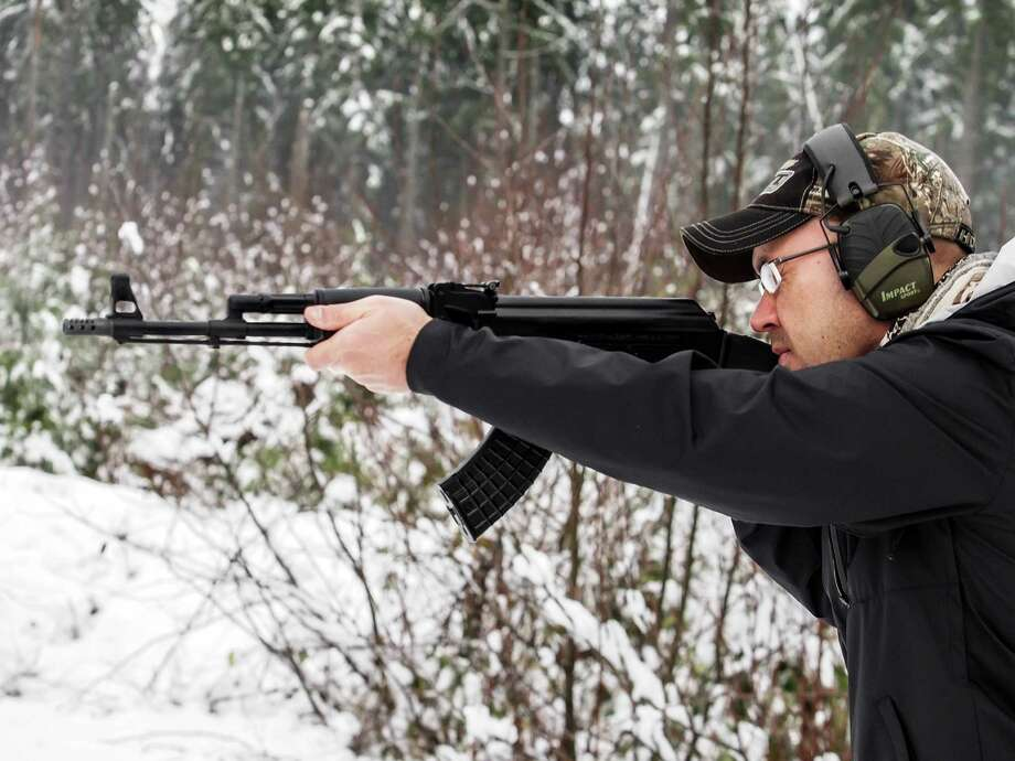 2012: An American man with a baseball cap and ear protection fires an AK-47 rifle in the woods with snow on the ground. Photo: Paula Thomas, Getty Images / © 2012 Paula Thomas