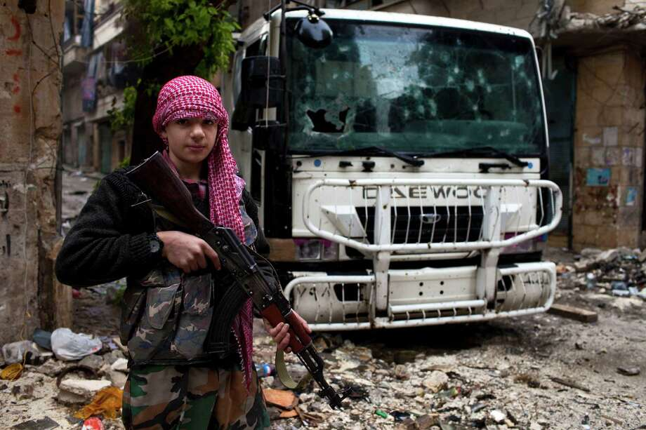 2012: Syrian teenager Abdel Khader Zeidan, 15, poses next to a checkpoint in the Salahadine district of Aleppo. Photo: STR, Getty Images / 2013 AFP