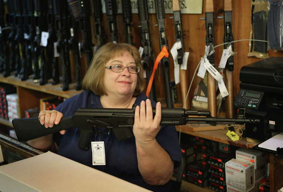 2012: Cindy Sparr boxes a AK-47 style rifle purchased by a customer at Freddie Bear Sports sporting goods store in Tinley Park, Illinois. Americans purchased a record number of guns in 2012 and gun makers have reported a record high in demand. Photo: Scott Olson, Getty Images / 2012 Getty Images