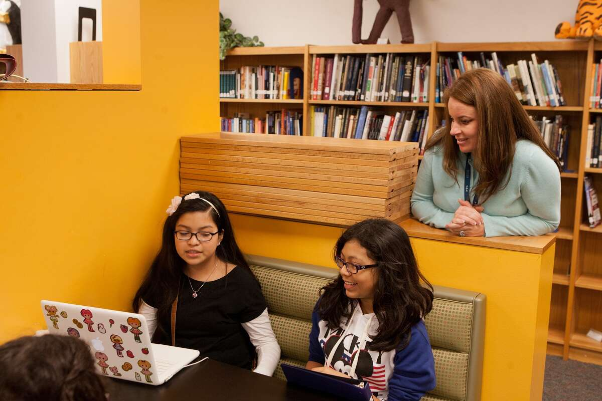 Jennifer Collier, director of Westchester Academy for International Studies, watches seventh-graders Angela Teco, 12, left, and Jacqueline Mendoza, 12, work on a Google Earth tour of Texas topography.