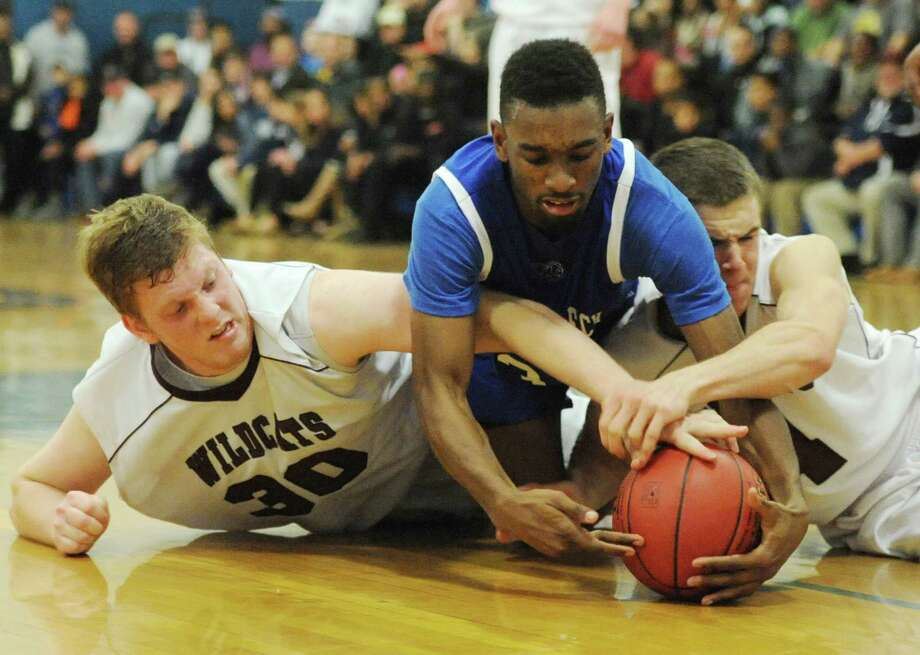 Bethel's Ian Melvin, left, and Will Daniels, right, fight for a loose ball with Abbott Tech's Asante Johnson in Abbott Tech's 72-67 win over Bethel in the first round of the News-Times Greater Danbury Tipoff Classic at the War Memorial Building in Danbury, Conn. on Thursday, Dec. 19, 2013. Photo: Tyler Sizemore / The News-Times