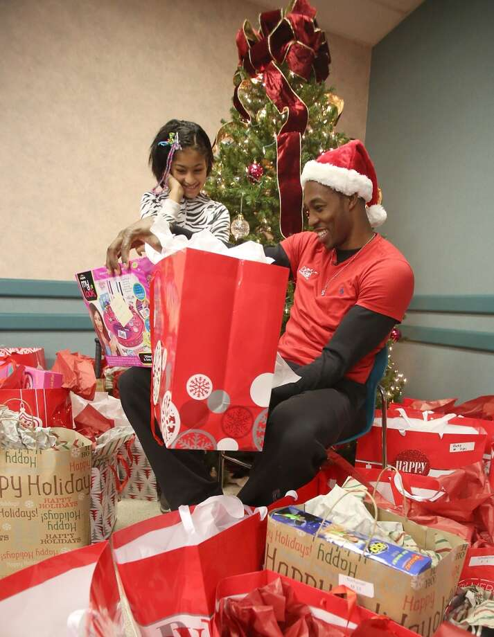 Dajanae Wright, age 10, smiles as Dwight Howard hands her a Christmas present. The Rockets center and his D12 Foundation spread some holiday cheer by serving breakfast and giving presents to 30 families at the Salvation Army Family Residence in Houston on Sunday. Photo: Thomas B. Shea, For The Chronicle