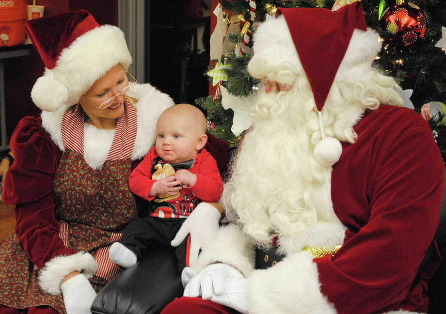 Santa and Mrs. Claus visit with 4-month-old Karson Sanders of Alvin.