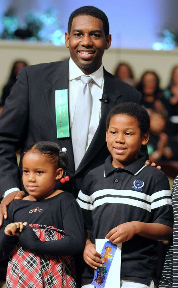 Reverend Roche Coleman, Senior Pastor Impact Church of The Woodlands, presents Joseph Forney, Bush Elementary fourth grader, his award for winning the MLK Poster Contest. at the 24th Annual Commemorative Celebration Honoring Dr. Martin Luther King Jr. at The Woodlands United Methodist Church.  Forney's little sister, Johanna, smiles at the applause for her big brother.David Hopper photograph Photo: David Hopper, Freelance / freelance
