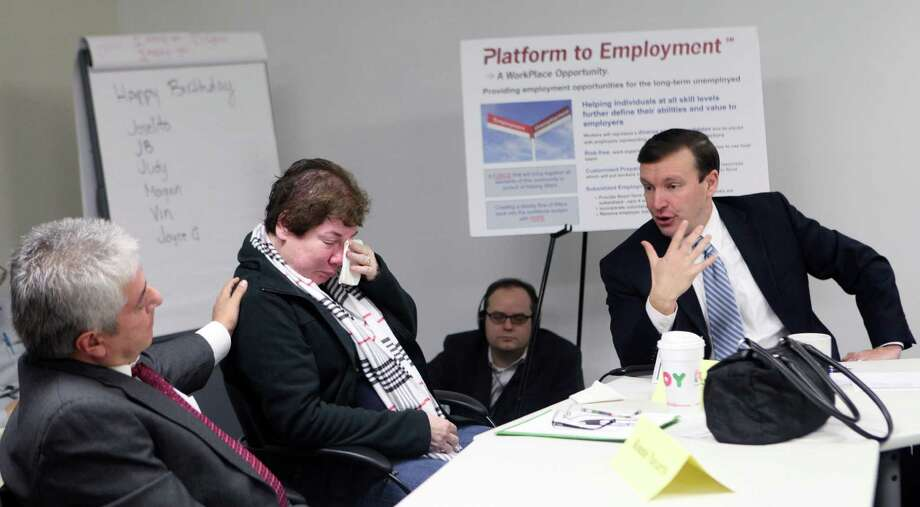 Ronnie Navarro, left, comforts Arlene Briere, during a meeting to discuss their stories of unemployment with Senator Chris Murphy at the WorkPlace in Bridgeport, Conn. on Monday, Dec. 23, 2013. Photo: Unknown, B.K. Angeletti / Connecticut Post freelance B.K. Angeletti