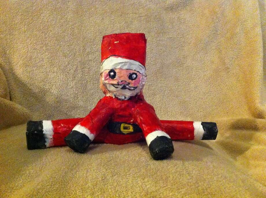 """Sheila Keyes, Kingwood: At 10 years old ,our precious daughter Natalie (now 23), was given an assignment by her art teacher to make a Santa with newspaper paper mache over cardboard tubes.  The entire class made standing Santas, but our creative child who also loved gymnastics decided her Santa should be doing the splits.  My Christmas decor would not be complete without Natalie's """"Splitting Santa""""."""