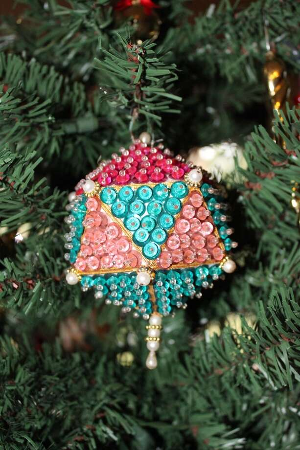 Alicia Buescher League City: December 1970 I was expecting my first child. To pass the time my mother-in-law brought me a little kit to make Christmas ornaments.  She and I would sit for hours working with the tiny beads, pearls, tassels creating these lovely ornaments that by todays standards are quite UGLY!  But every Christmas I hang the six remaining ornaments on a smaller special tree, where I also hang all the ornaments the kids have made me over the years . . . reindeers made of cloths pins, candy canes made of beads, trees made of wood, stars made of felt and wreaths made of yarn.  We still put up the big Christmas tree, but the smaller tree is one everyone gathers around and looks for their ornament masterpiece they made when they were young.  But the ornaments I hold so dear are the ones I made for my daughter Paige, 43 years ago, with my mother-in-law Peggy.  The biggest treasure is not only the ugly ornament, but Peggy who helped me make them so many years ago.  Peggy is now 91 and she smiles when she sees the ornaments hanging on the special tree and she tells our granddaughter Avery how her grandmother and great-grandmother spent the holidays making those beautifully ugly ornaments for her mother.